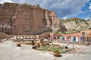 Vistors relax in the pools below rugged cliffs at the Ojo Caliente Mineral Springs Resort and Spa near the village of Ojo Caliente in northern New Mexico.